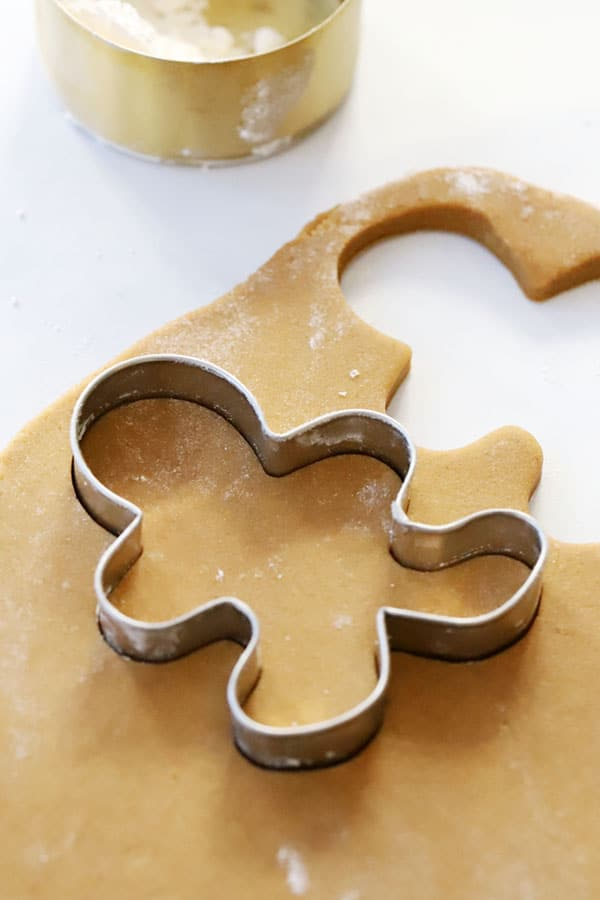 Gingerbread cookie dough rolled out and being cut with a cookie cutter.