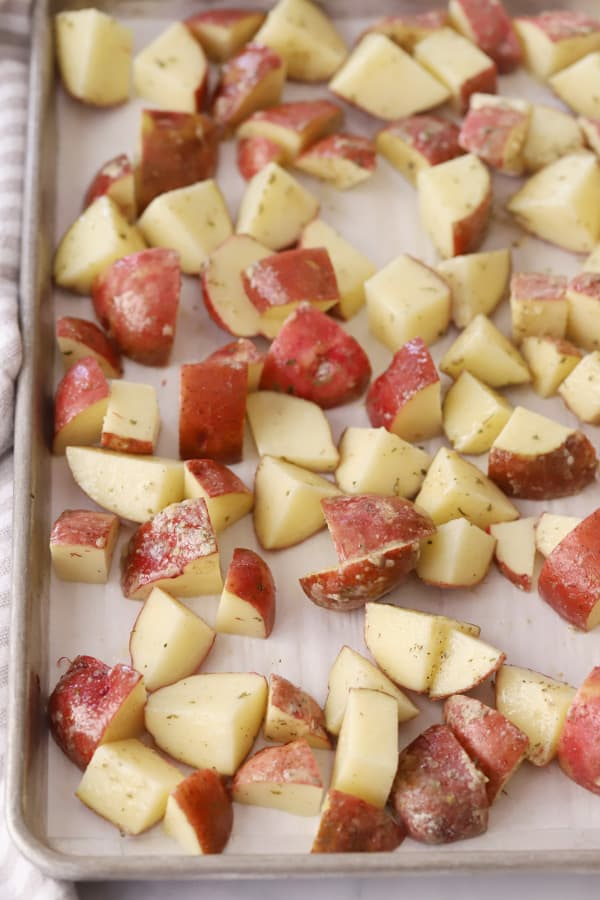 Quartered red potatoes on a baking sheet ready to roast.