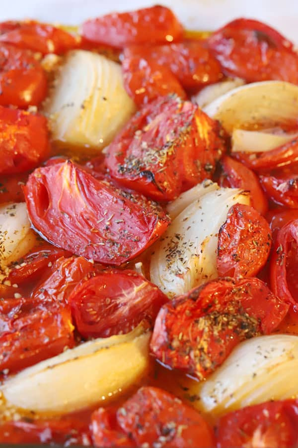 roasted tomatoes and onions in a glass baking dish