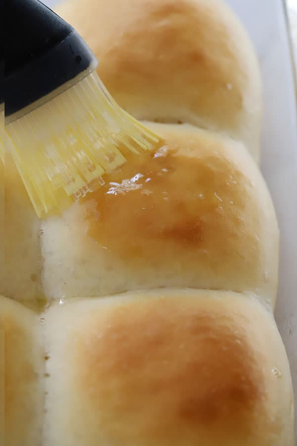 Quick Dinner Rolls being brushed with melted butter.