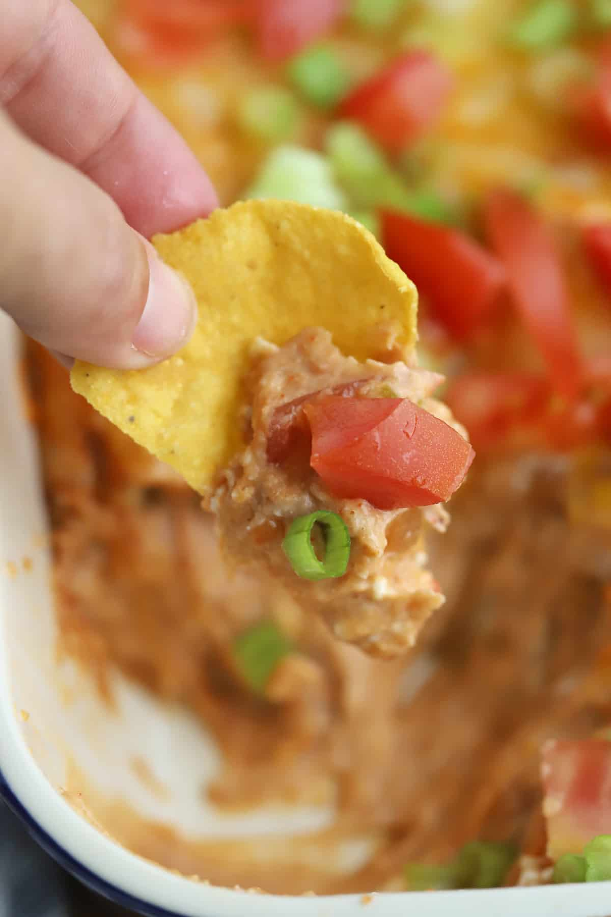 A hand holding a tortilla chip that has been dipped into Cheesy Bean Dip.