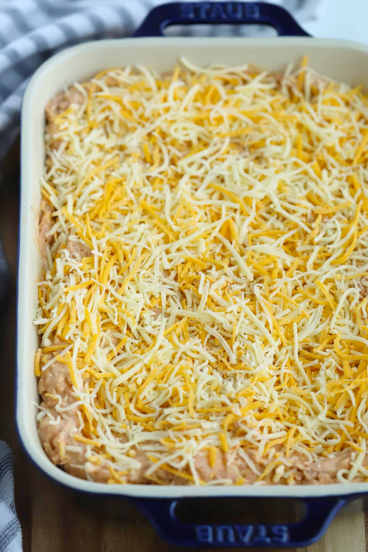 A baking dish filled with a refried bean mixture and topped with shredded cheese.