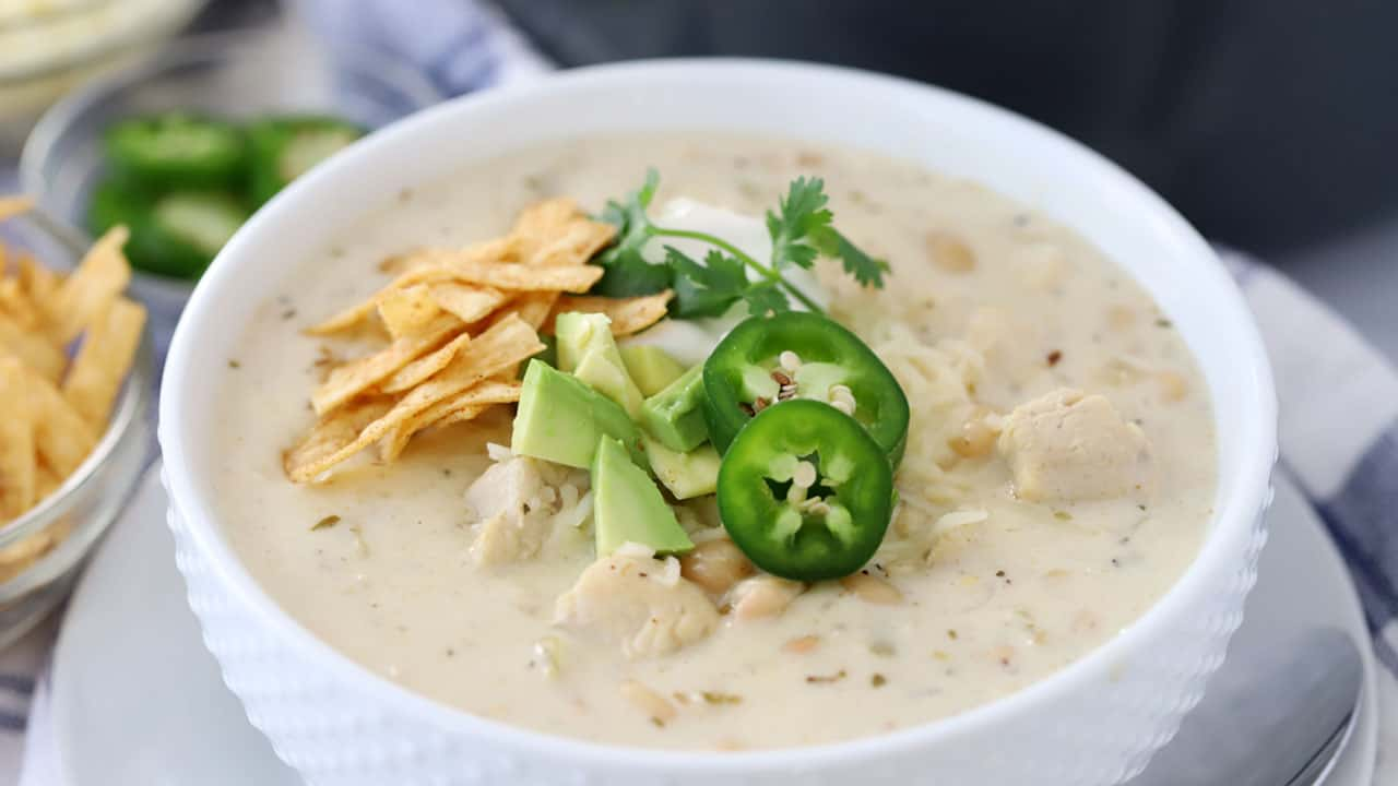A bowl full of white chicken chili with toppings.