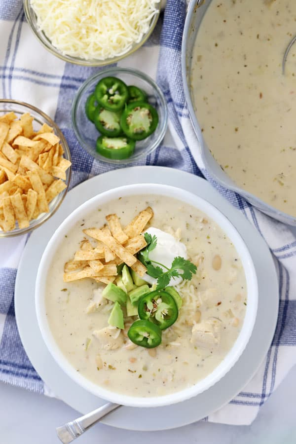 A bowl of white chicken chili with toppings of sour cream, shredded cheese, sliced jalapenos and tortilla strips.