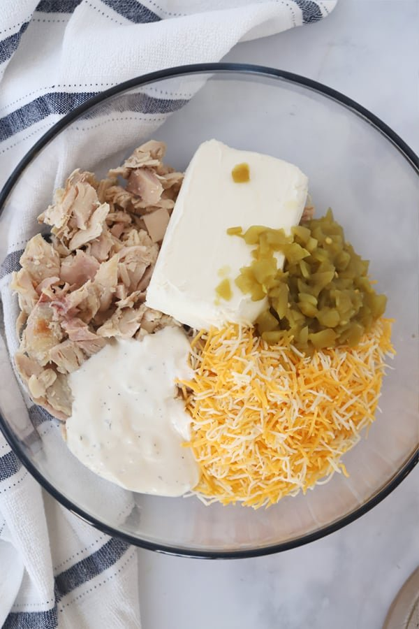 A glass bowl filled with cream cheese, shredded chicken, ranch dressing, green chili and cheddar cheese.