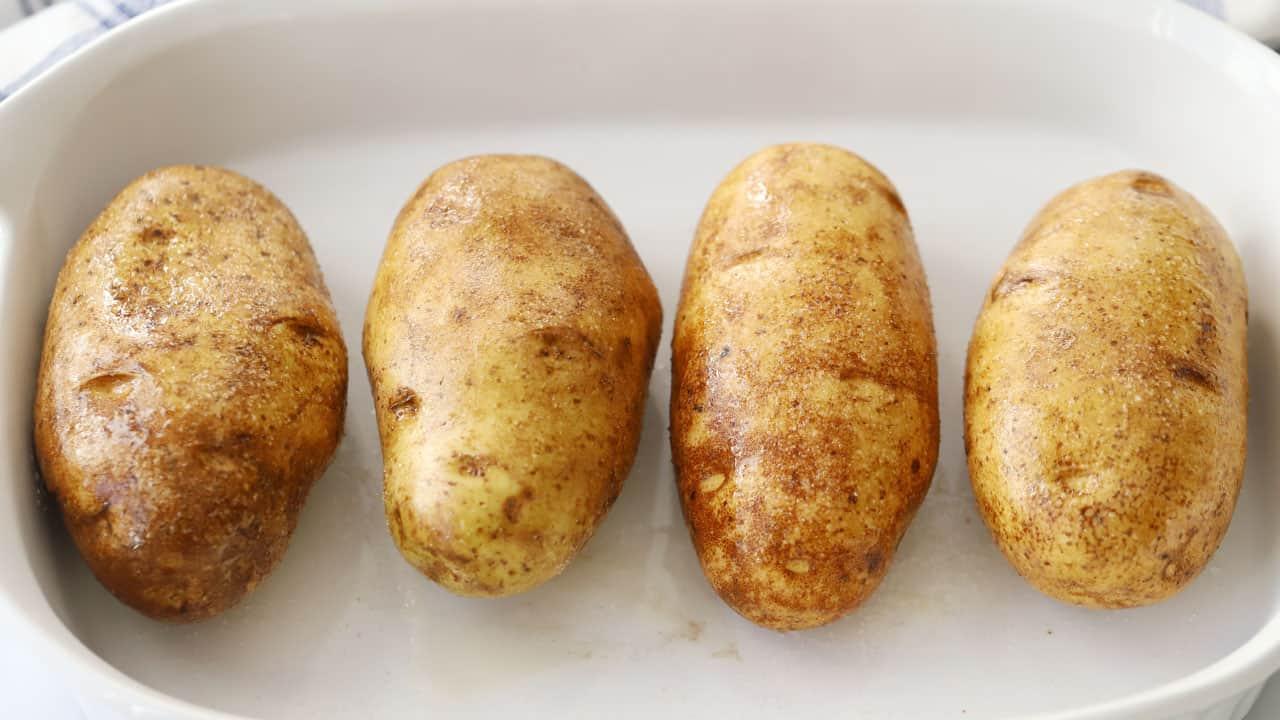 Four russet potatoes inside a baking dish.