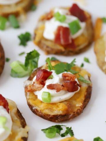 Crispy potato bites garnished with sour cream, bacon and fresh greens.