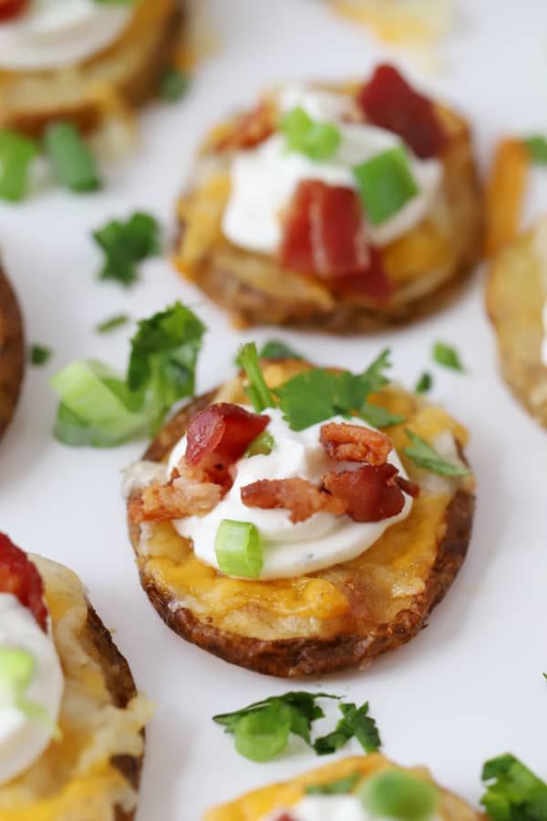 Crispy potato bites garnished with sour cream, bacon and fresh greens.