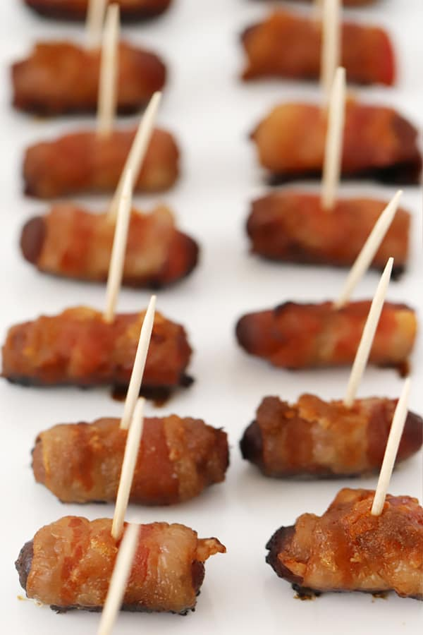 Bacon wrapped smokies with toothpicks on a baking sheet.