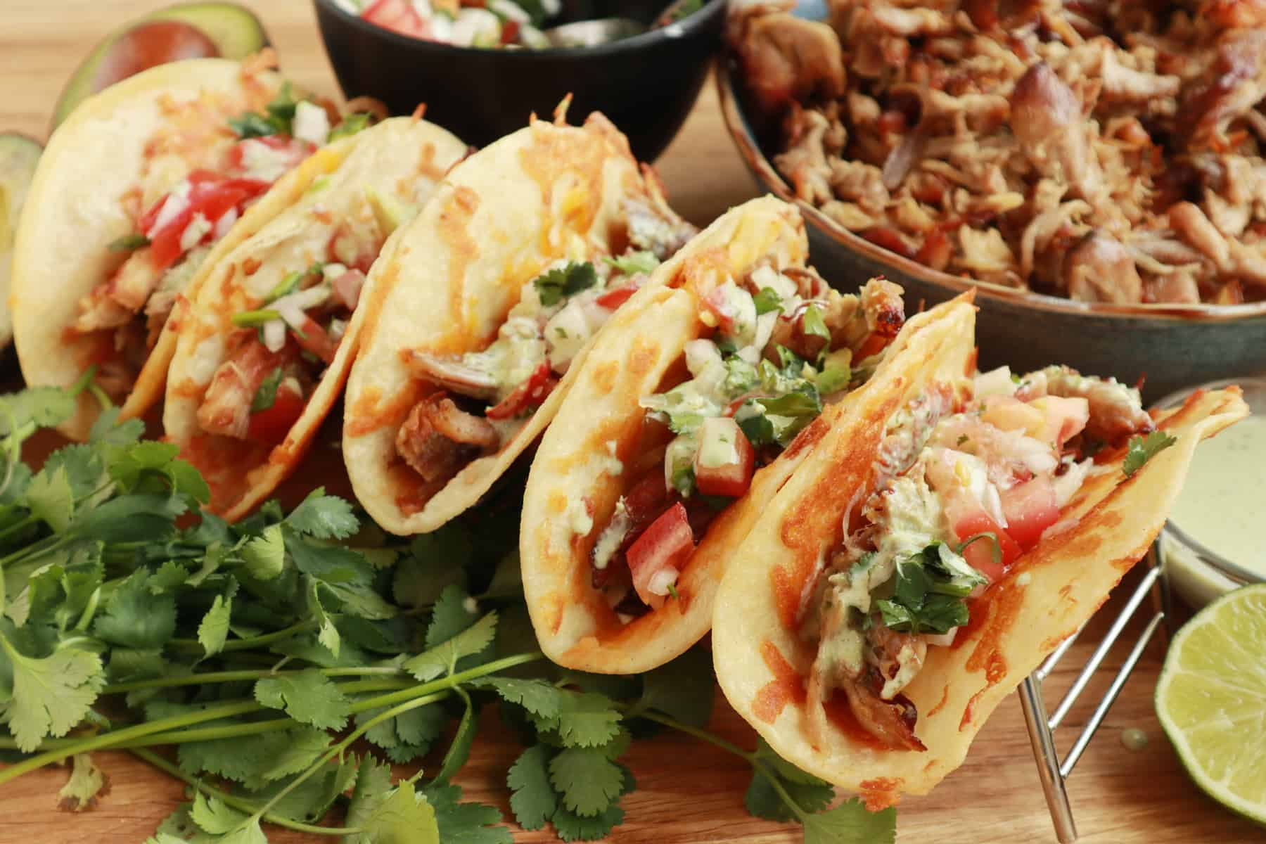Tacos lined up and ready to serve on a table next to other ingredients for serving.