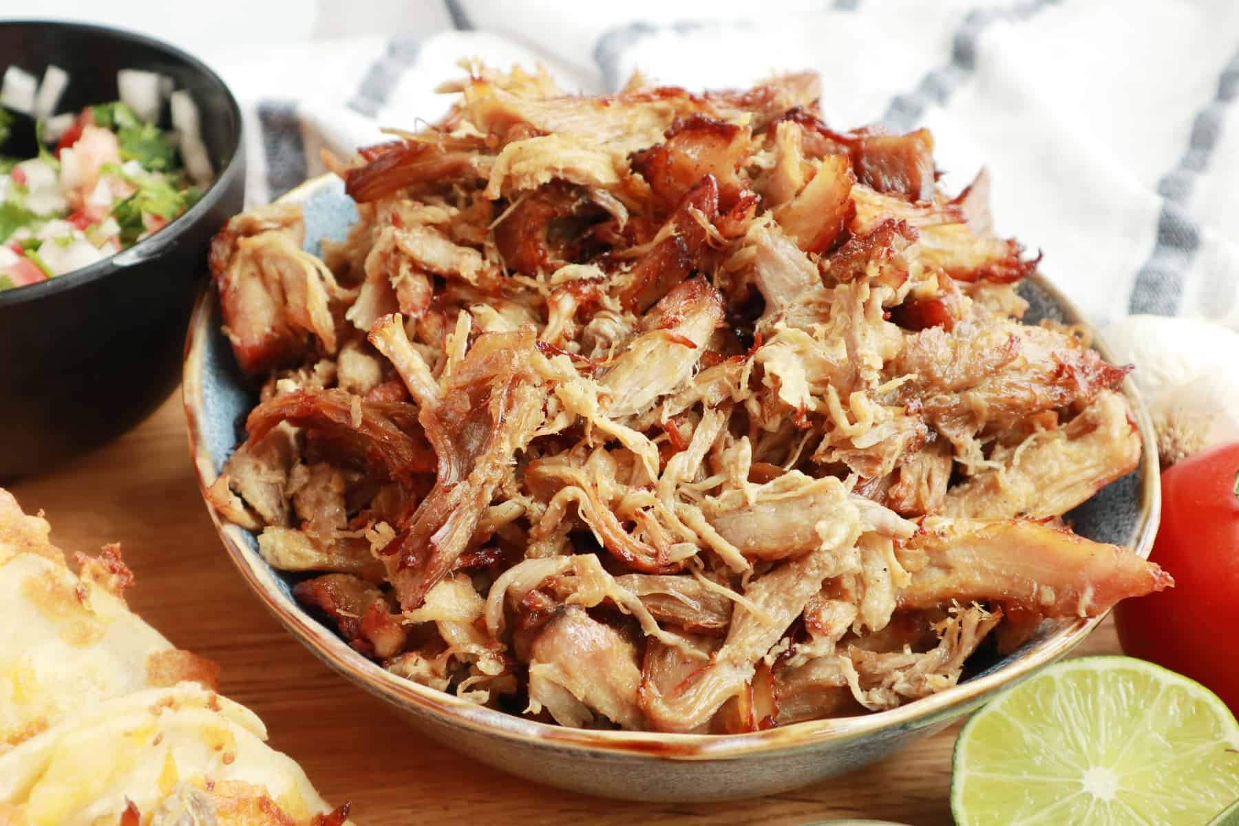 A bowl full of shredded pork carnitas on a table alongside a fresh lime and other toppings.