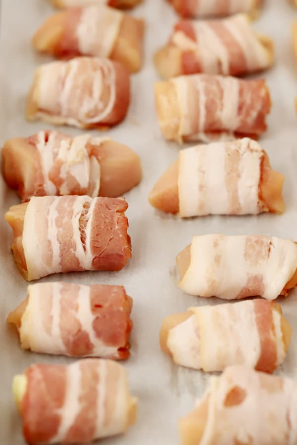 A sheet tray with rows of chicken chunks wrapped in bacon.