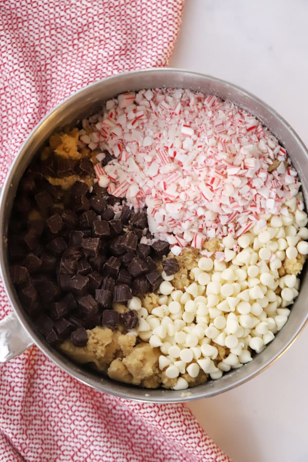 A mixing bowl filled with cookie dough and topped with dark chocolate chunks, white chocolate chips and candy cane pieces.