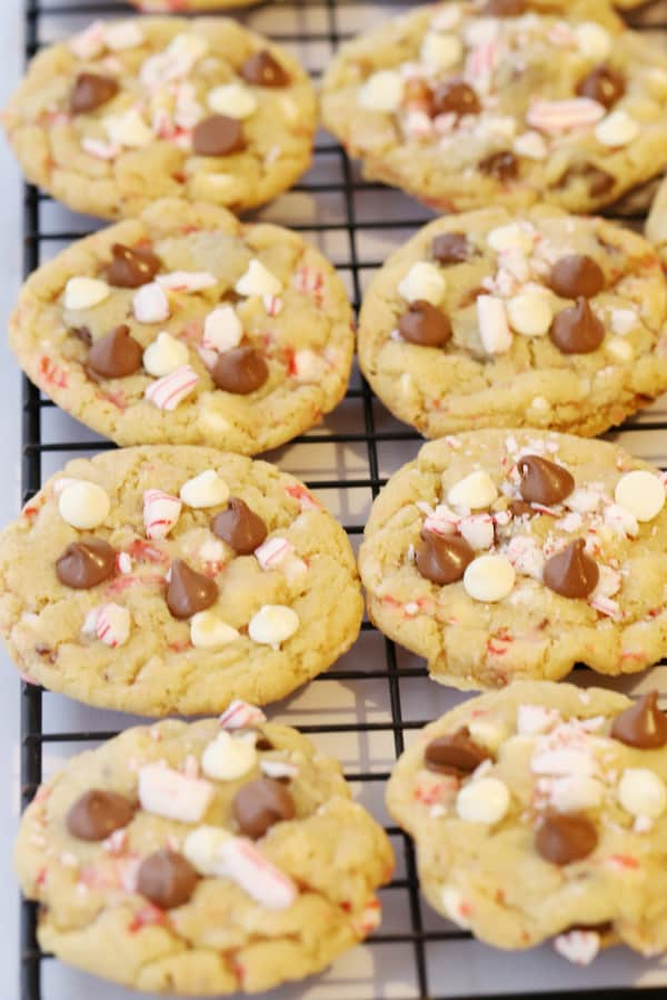 Fresh baked cookies cooling on a wire rack topped with chocolate chips and crushed candy canes.
