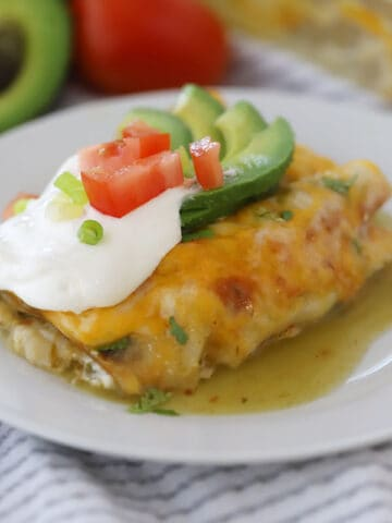 green chile chicken enchilada topped with sour cream, avocados,and tomatoes
