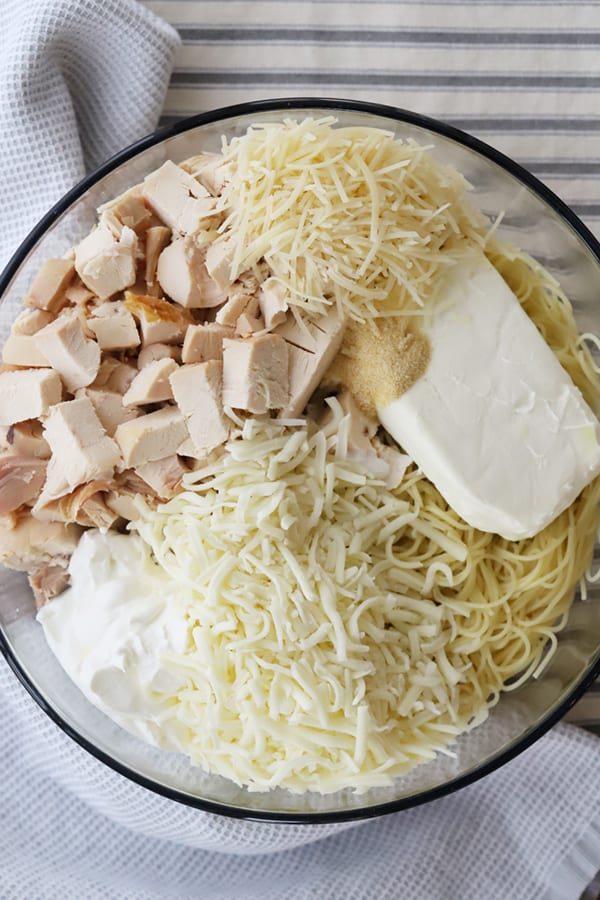 A glass mixing bowl with cheese, chicken, spaghetti and sour cream.