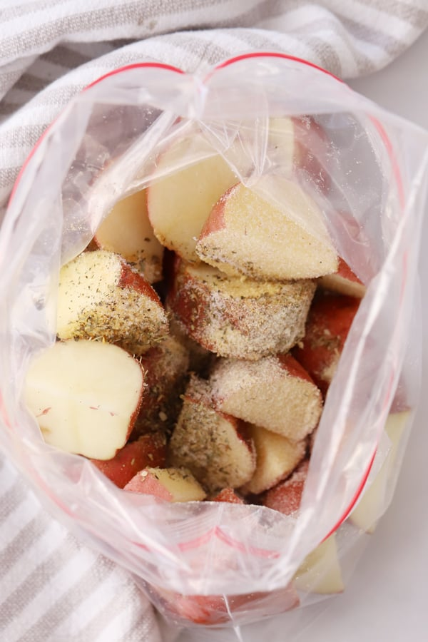 Red potatoes cut into quarters inside a ziplock bag, sprinkled with herbs and seasoning.