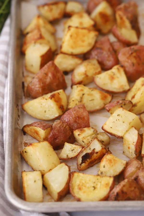 Oven Roasted red potatoes cut into pieces on a baking sheet.