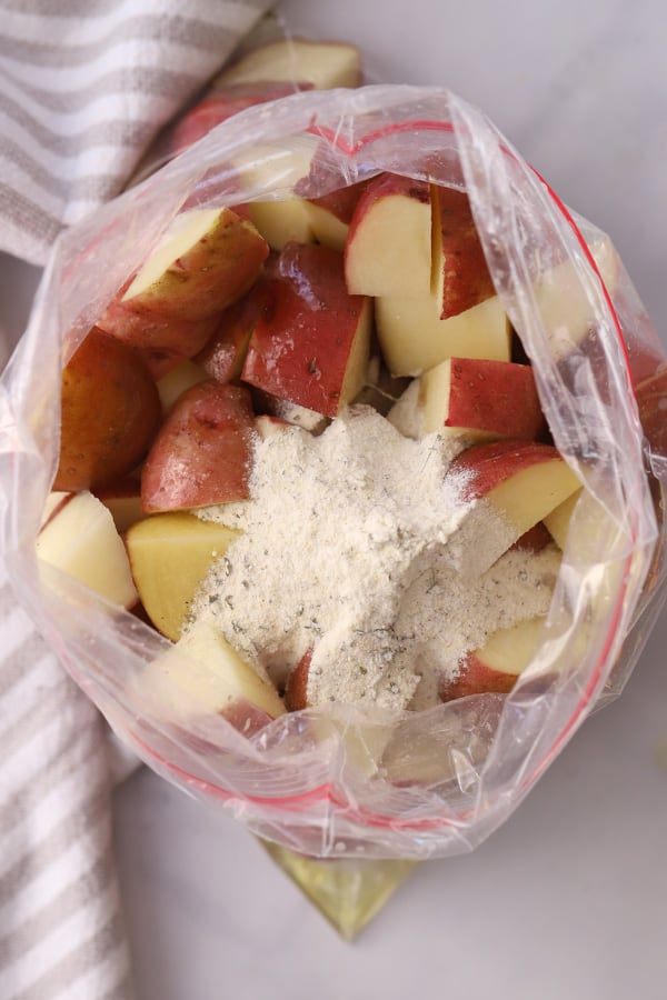 Quartered red potatoes in a ziplock bag topped with ranch dressing mix.