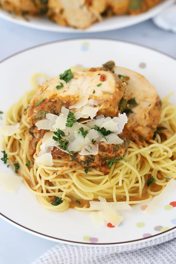 A plate full of Tuscan chicken on a bed of spaghetti topped with Parmesan cheese and fresh herbs.