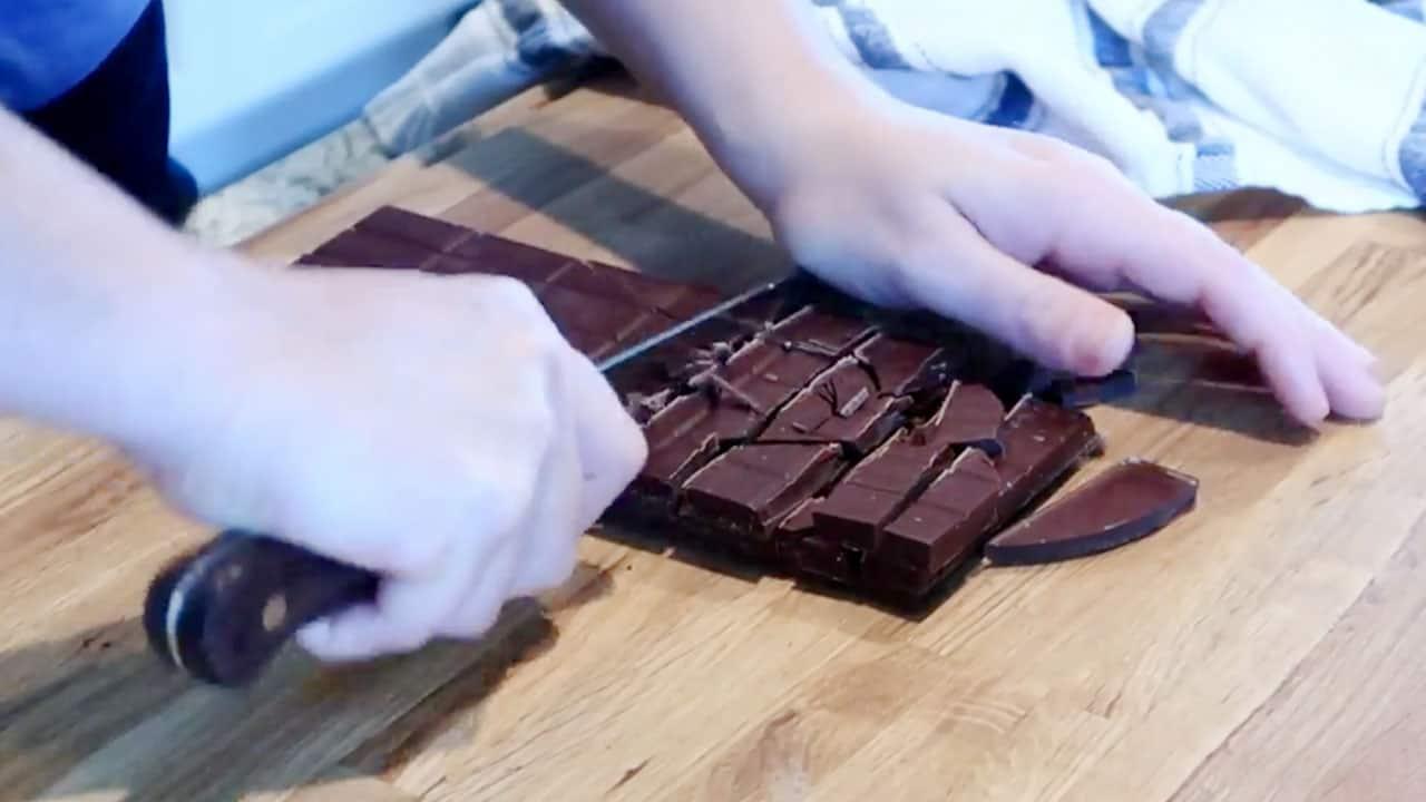 Chopping chocolate bar for chocolate fondue