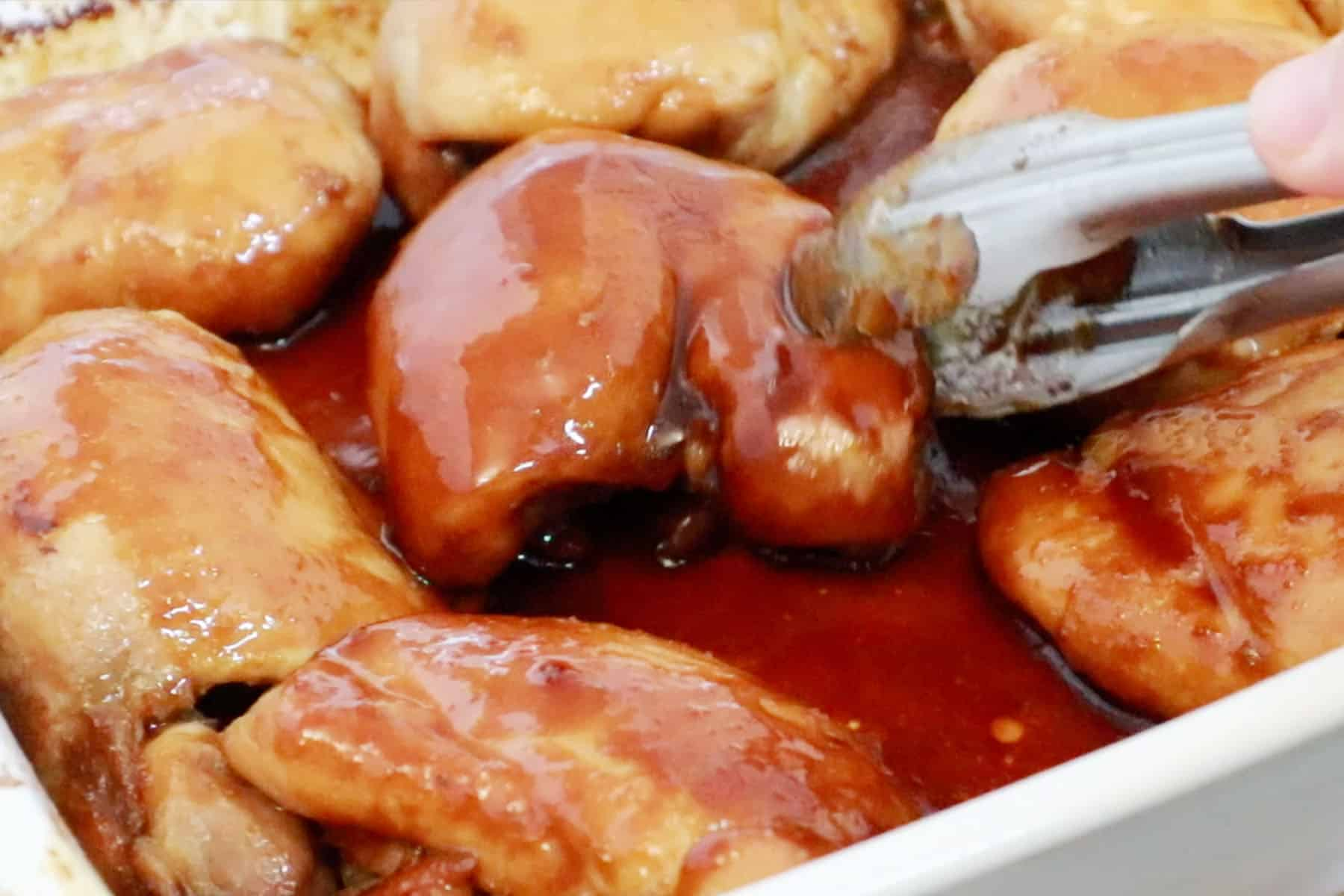 Honey Soy Chicken Thighs being turned over mid bake