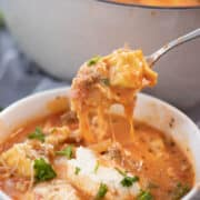 lasagna soup with cheese in a white bowl