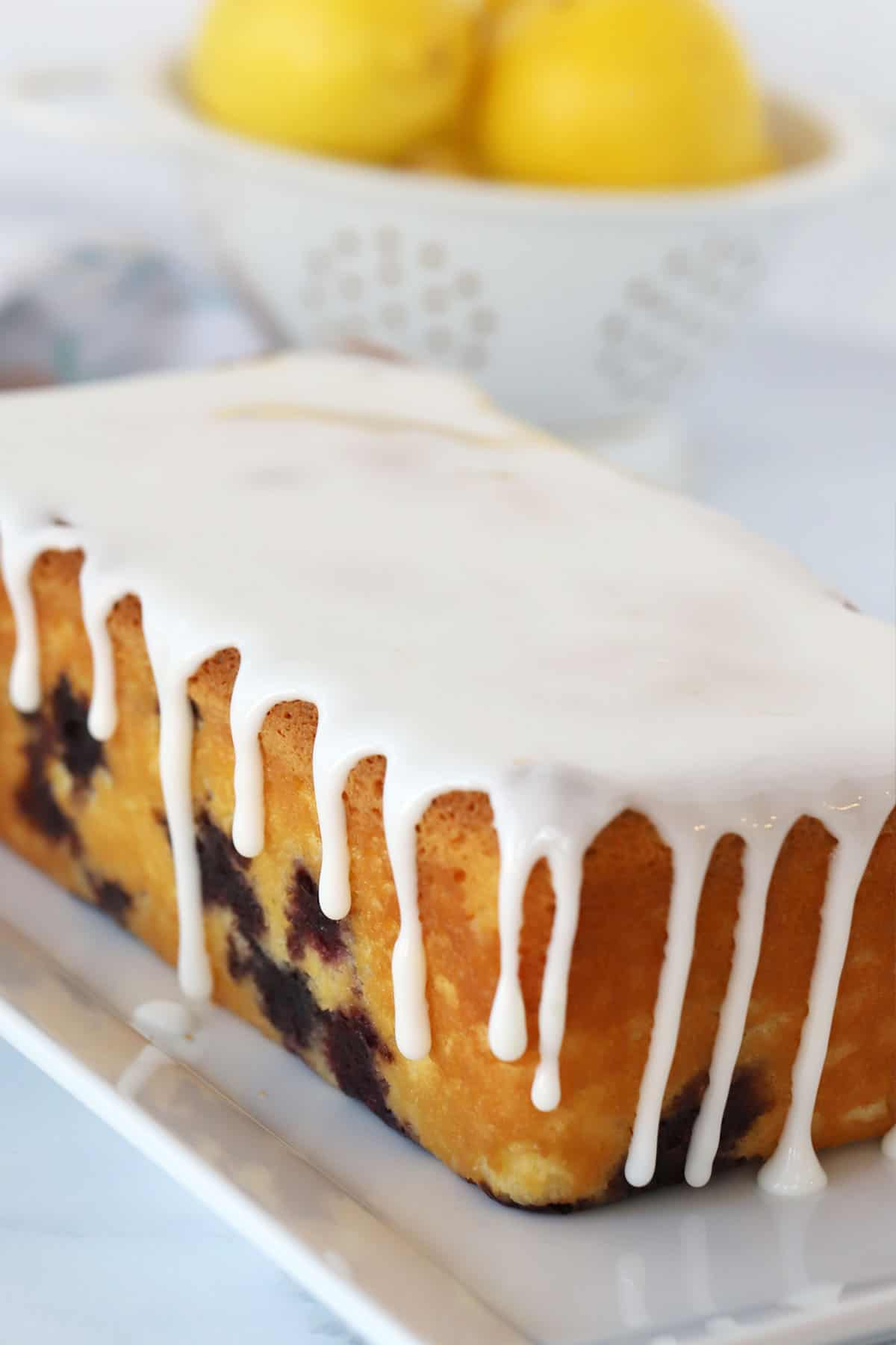 A full loaf of lemon blueberry bread on a white plate dripping with lemon glaze.