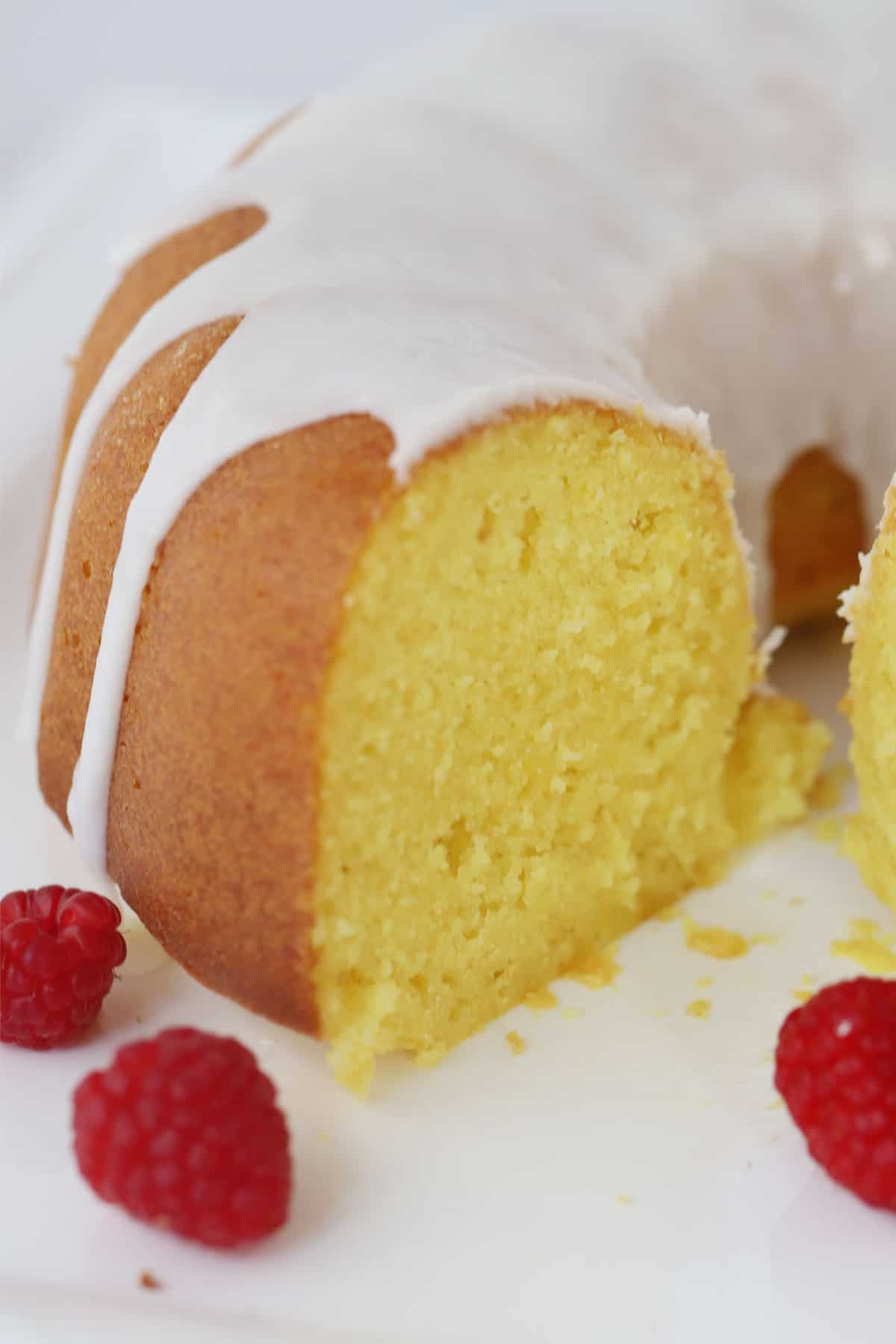 lemon bundt cake with lemon glaze and a few raspberries
