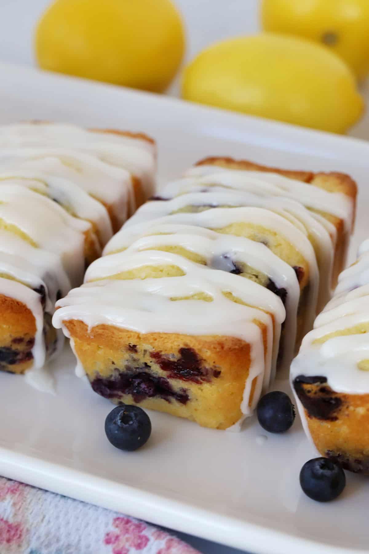 A side shot of mini lemon blueberry loaves with lemon glaze.