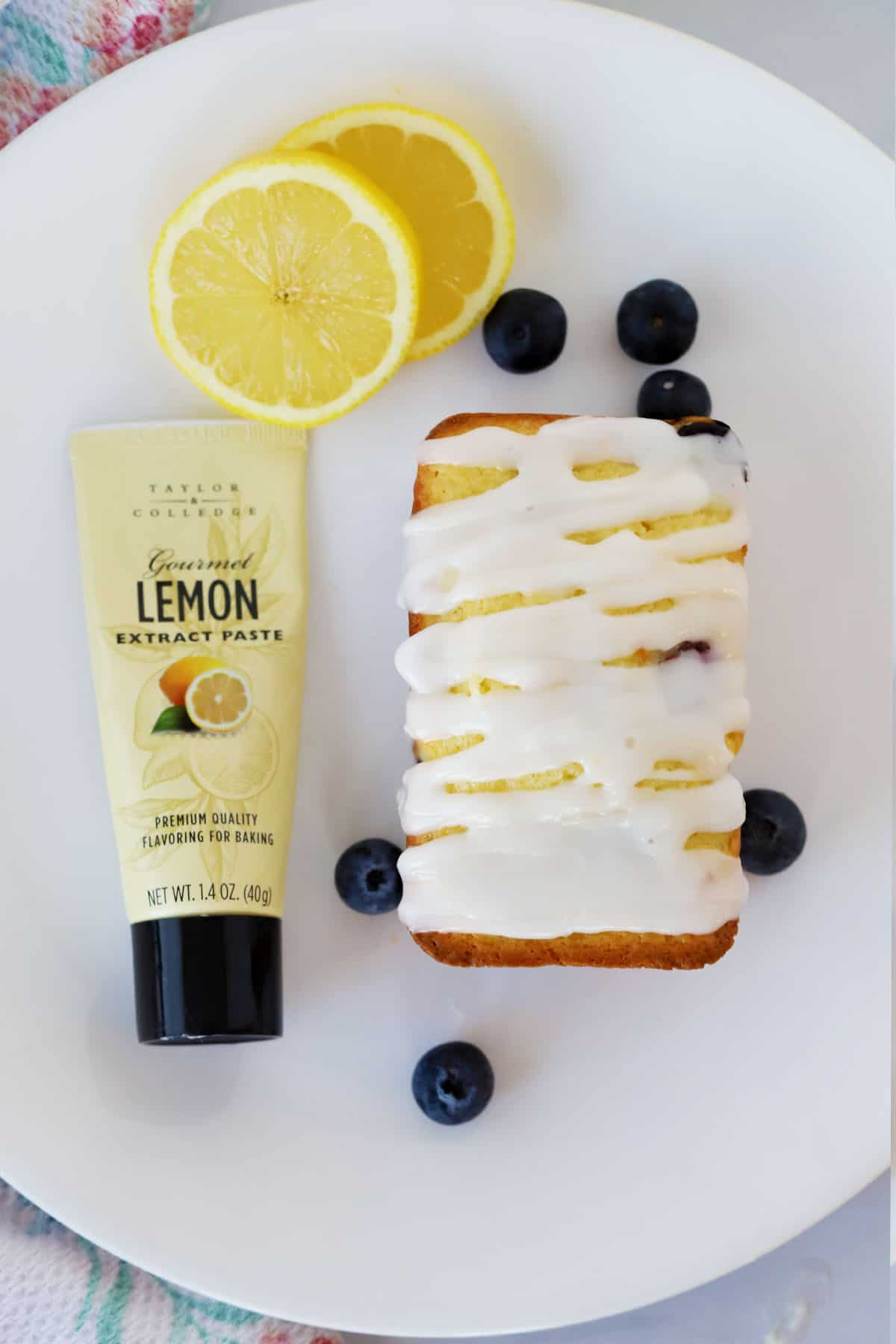 A white plate with a mini loaf covered in lemon glaze next to a bottle of lemon paste, fresh blueberries and a sliced lemon.
