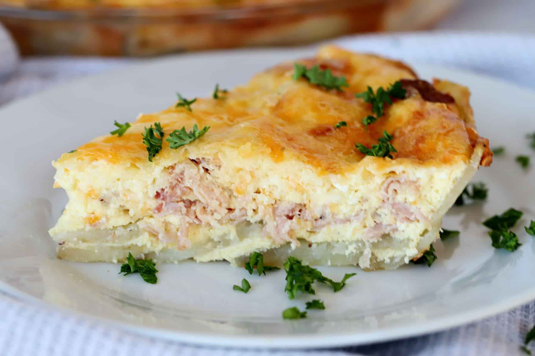 A slice of quiche on a white place with a potato crust and filled with ham and cheese, garnished with fresh parsley.