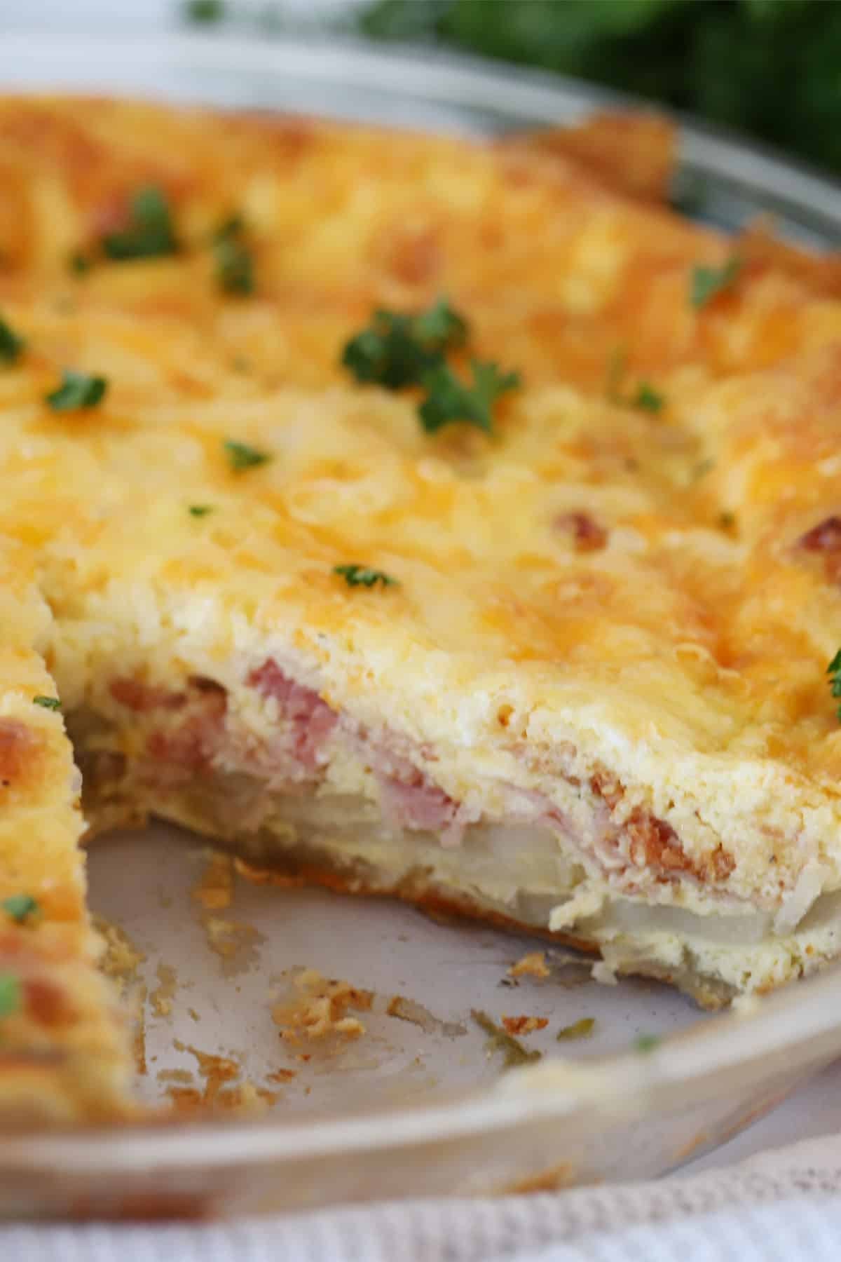 Baked quiche in a pie dish with a slice removed, garnished with fresh parsley.