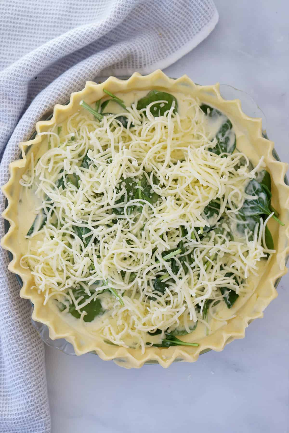 Crimped pie dough filled with custard, spinach and cheese ready to bake.