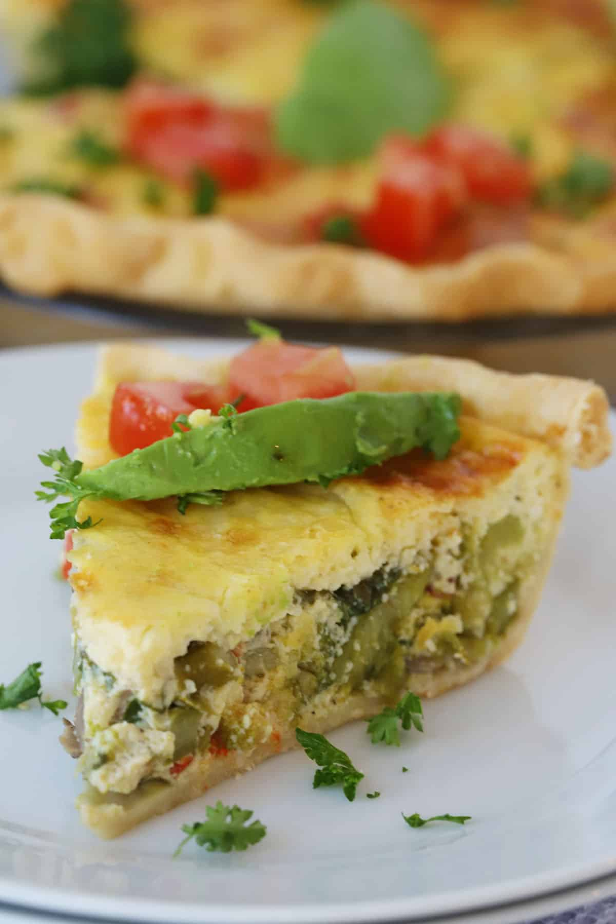 A slice of baked quiche on a white plate, topped with avocados and tomatoes.