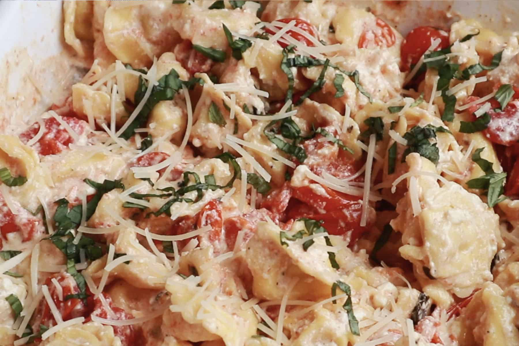 Feta pasta made with tortellini and garnished with Parmesan cheese and fresh basil.