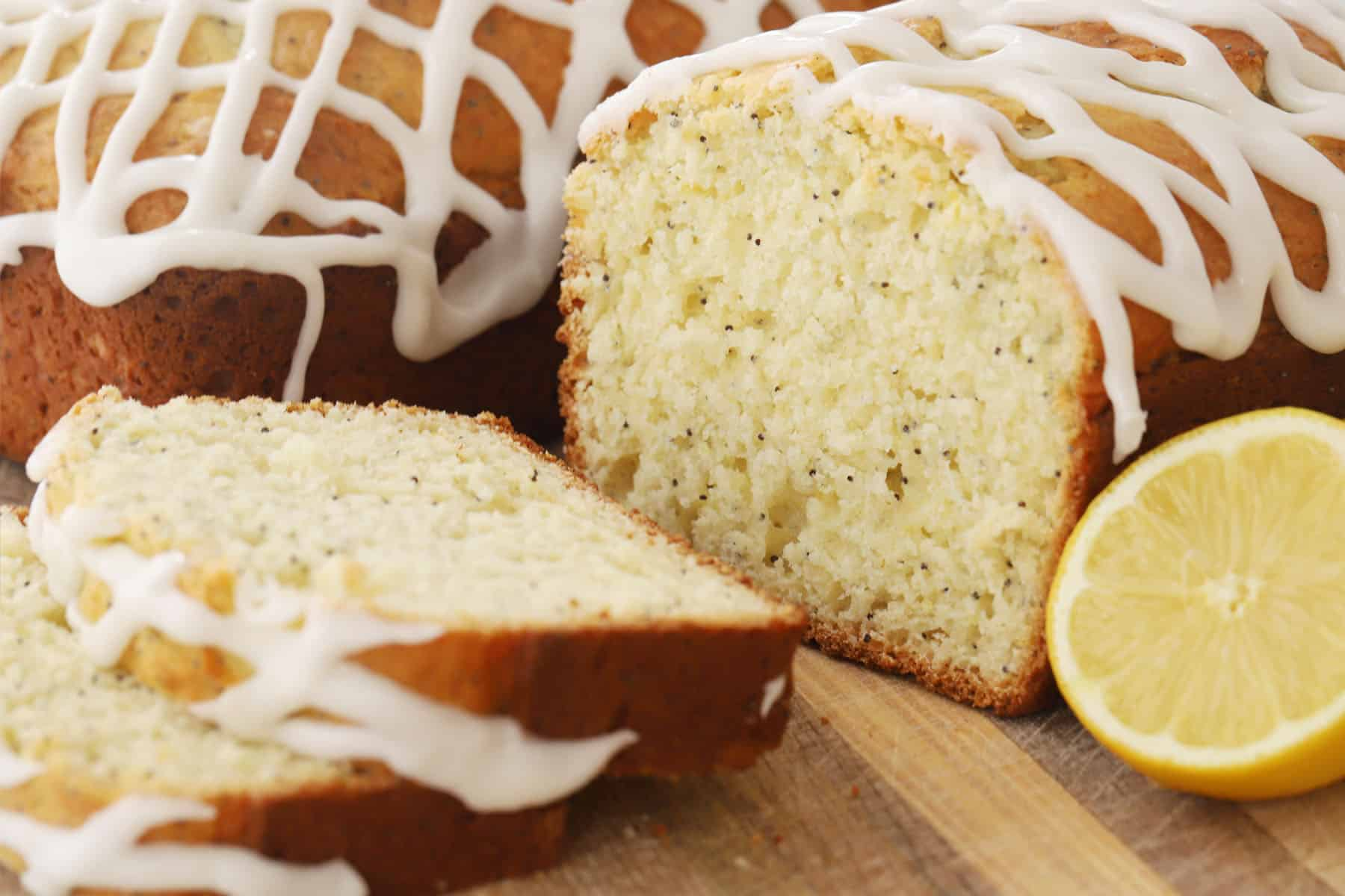 Loaves of lemon poppyseed bread topped with lemon glaze and sliced on a cutting board.