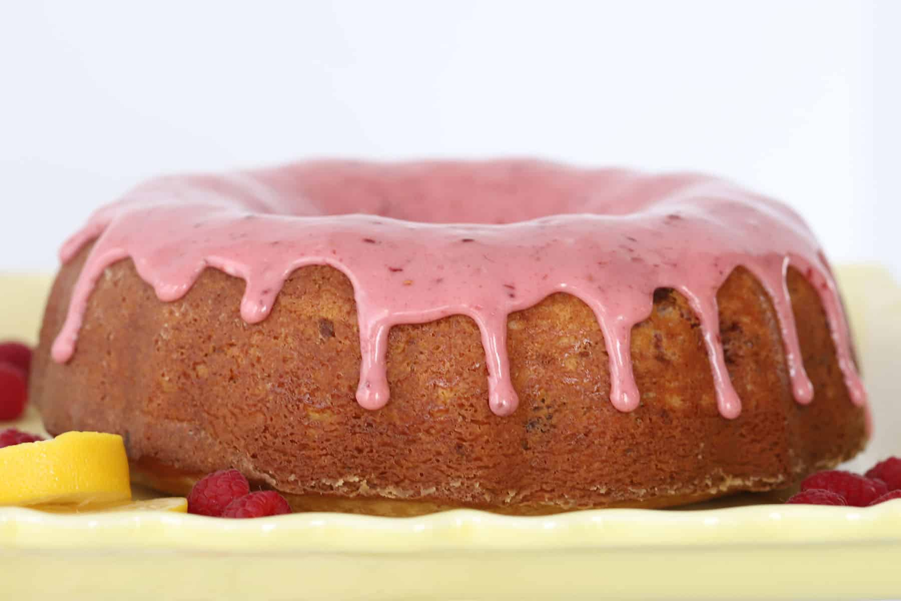 A full bundt cake on a serving plate topped with pink raspberry glaze.