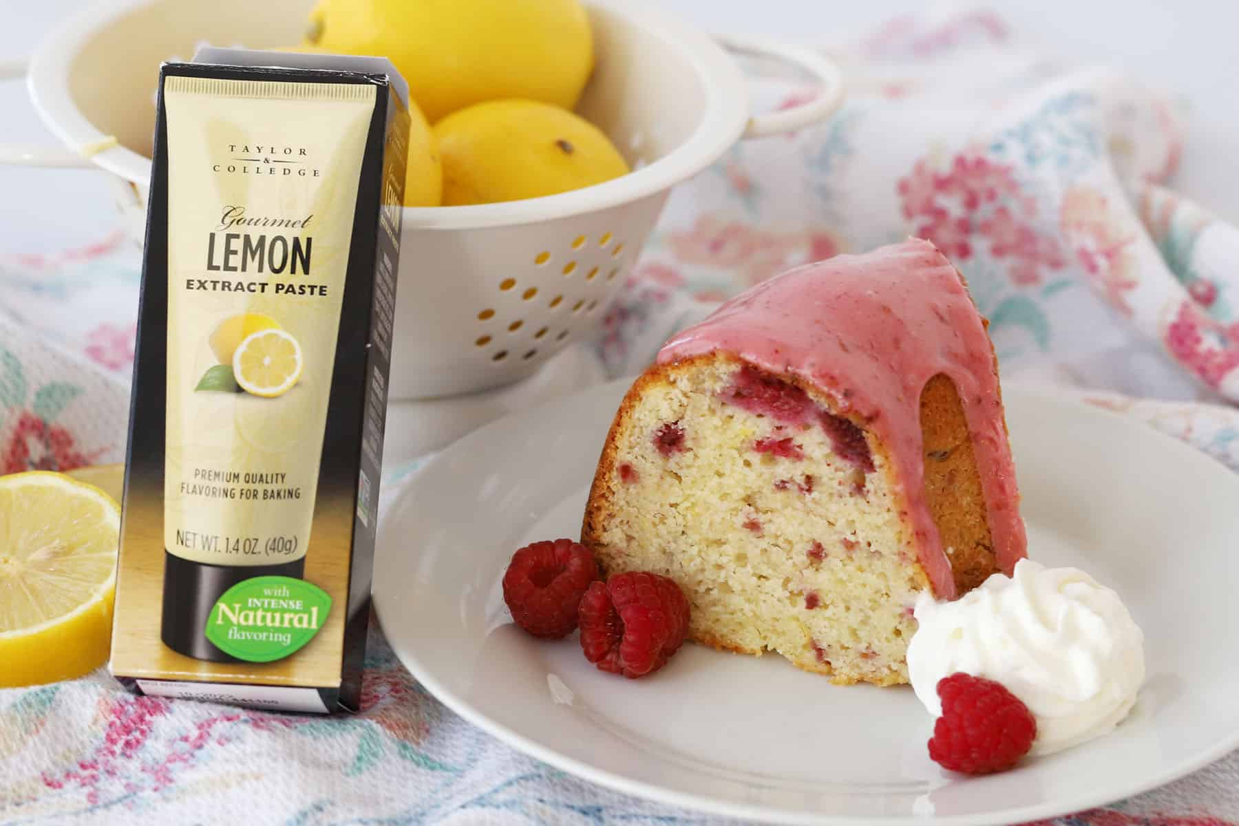 A slice of glazed bundt cake on a plate with whipped cream and raspberries, with a tube of lemon paste next to it.