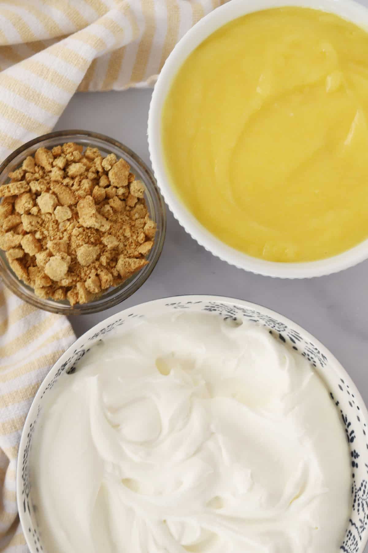 Three separate bowls filled with lemon curd, whipped cream and crushed graham crackers.