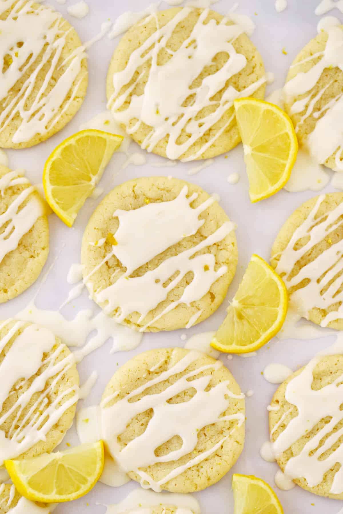 Baked cookies drizzled with glaze surrounded by fresh lemon wedges.