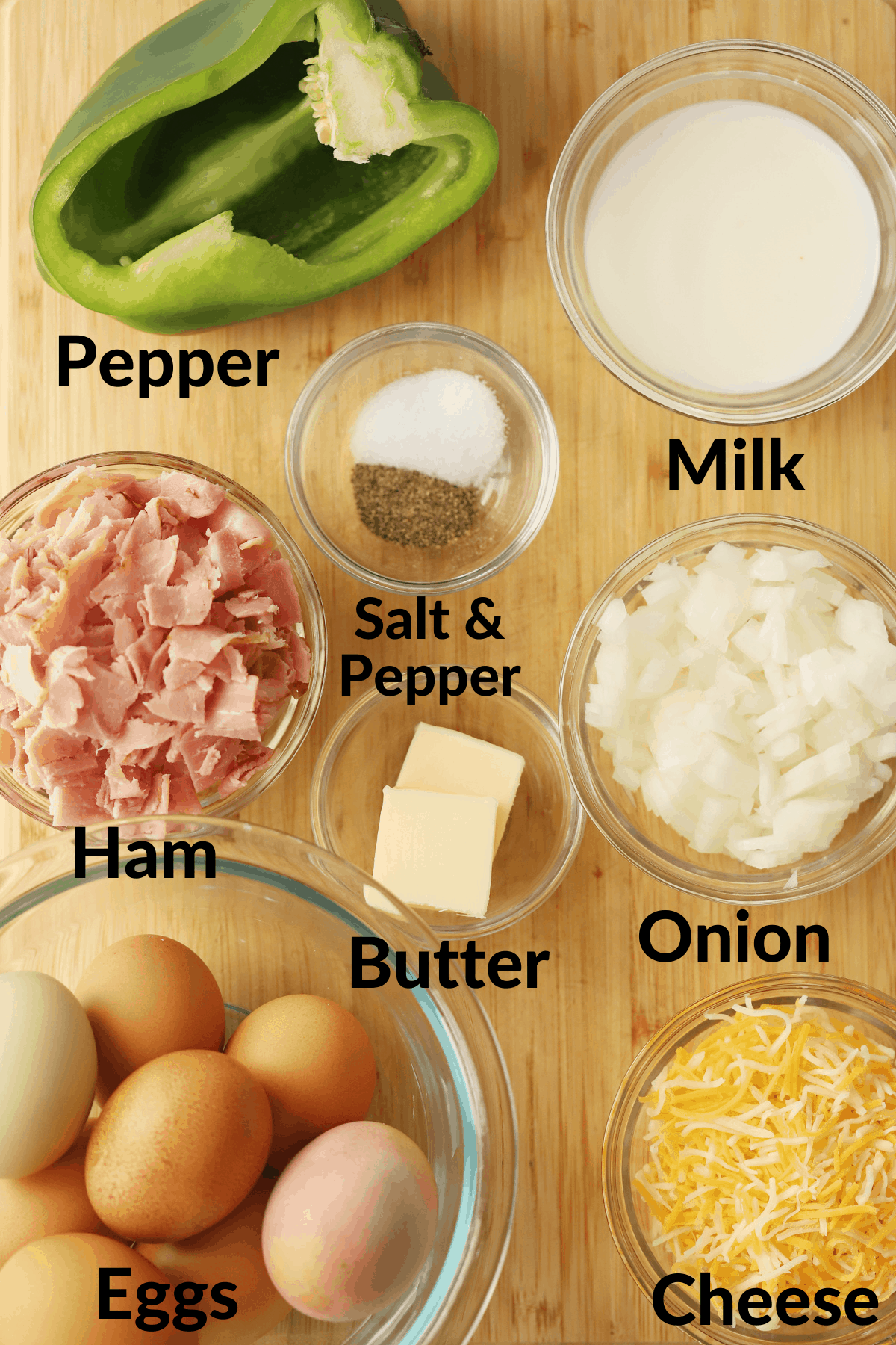 Separate ingredients for making this Baked Denver Omelet in small ramekins and bowls labeled with what they are.