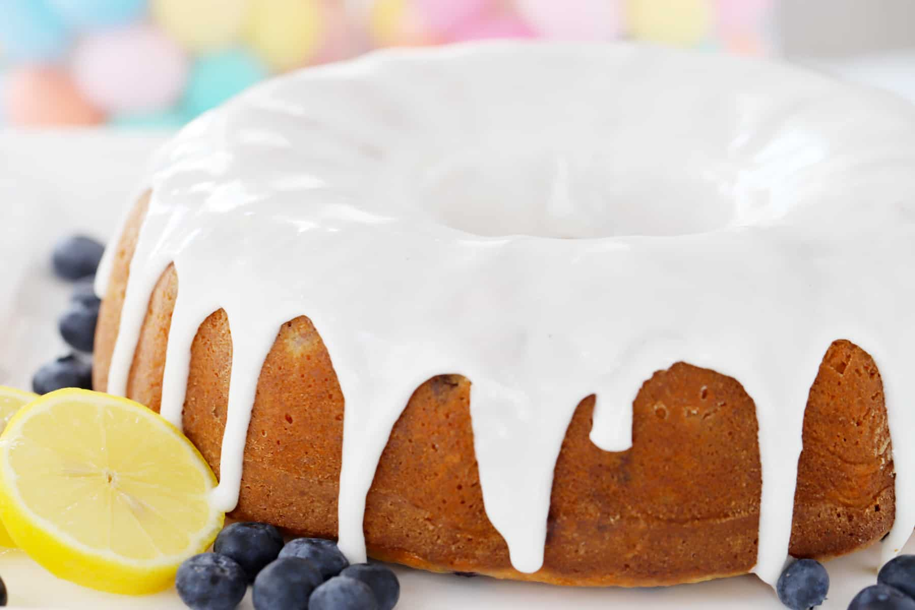 A whole glazed bundt cake on a white plate, garnished with fresh blueberries and lemon.