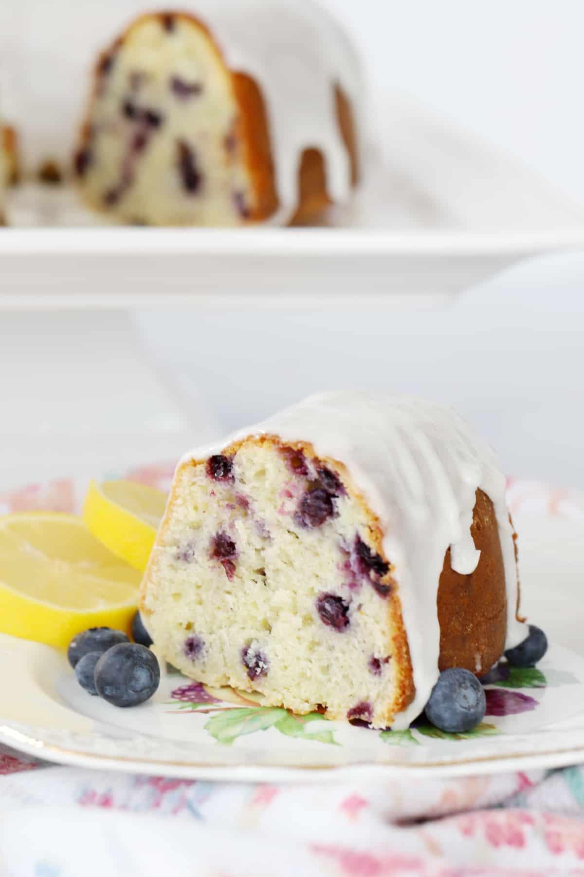 A slice of glazed blueberry bundt cake on a decorative place.