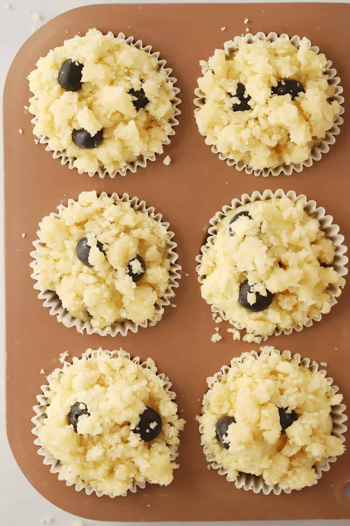 Muffins topped with blueberries and streusel in a muffin pan.