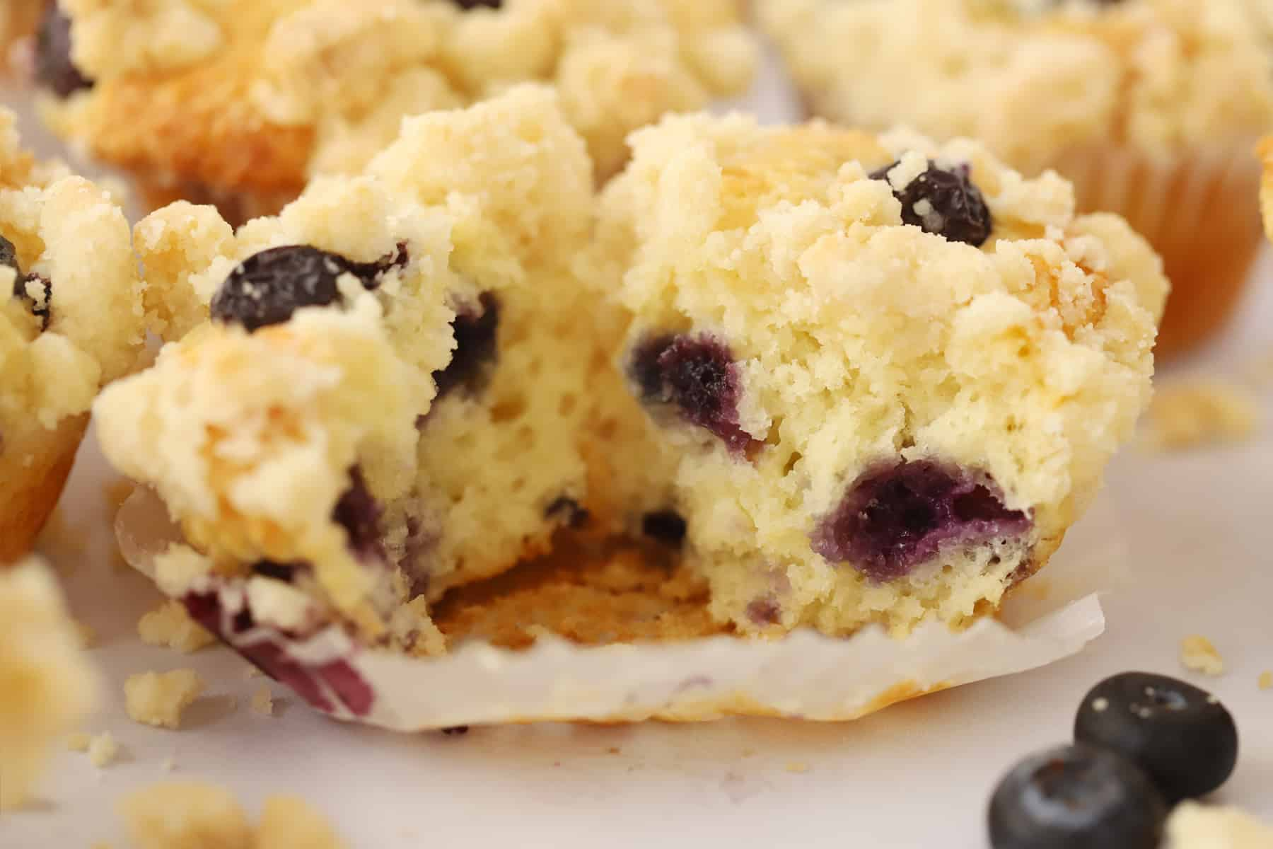 A lemon blueberry muffin broken in half ready to eat.