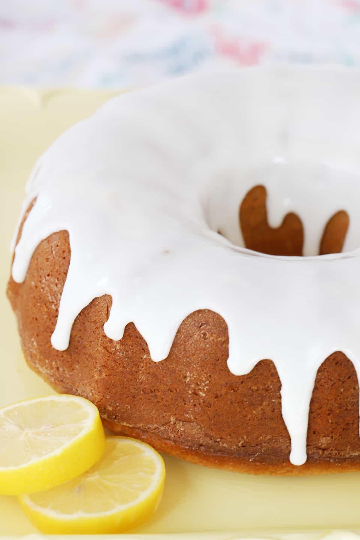 A whole glazed bundt cake on a serving platter with slices of fresh lemon.