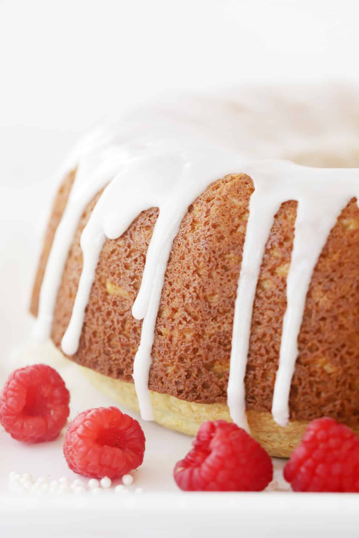 A glazed bundt cake garnished with fresh raspberries.