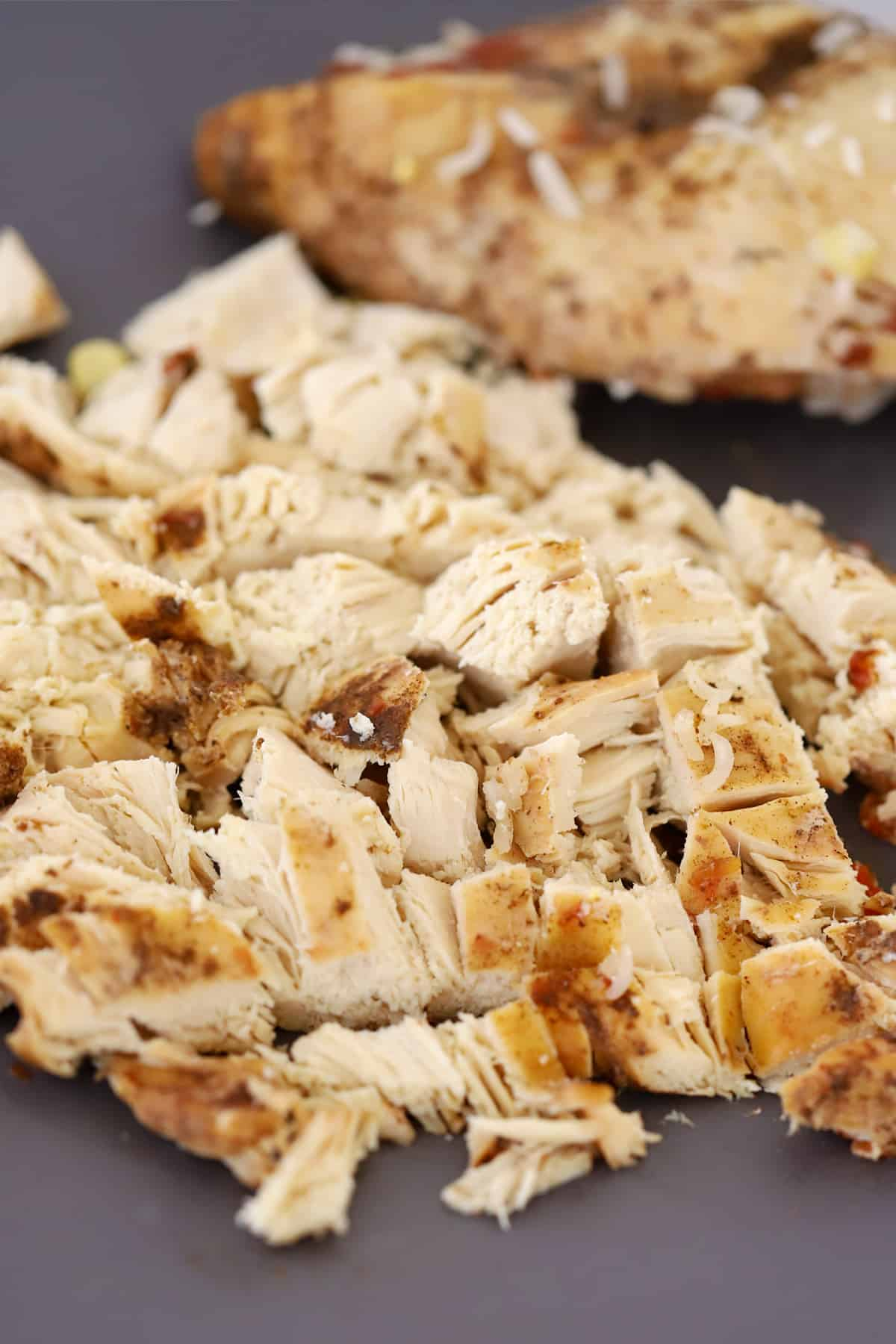 Diced, cooked chicken on a cutting board.