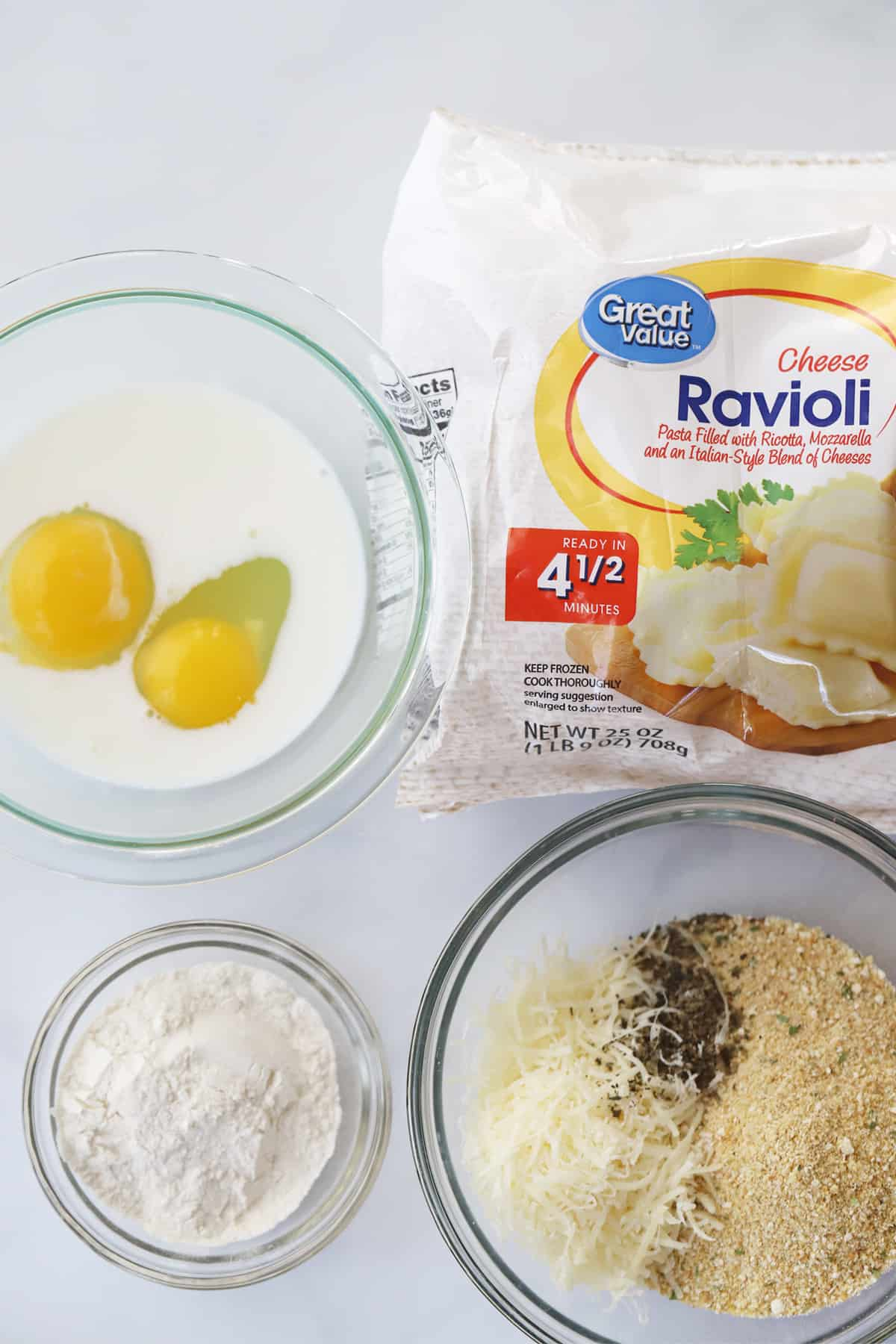 Three glass bowls filled with eggs and milk, flour, cheese, breadcrumbs, seasoning and a bag of raviolis.